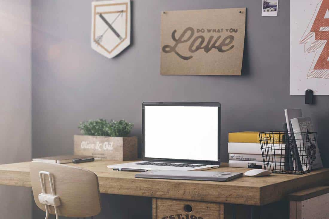 Stylish graphic designer's workspace with computer and posters at home or studio