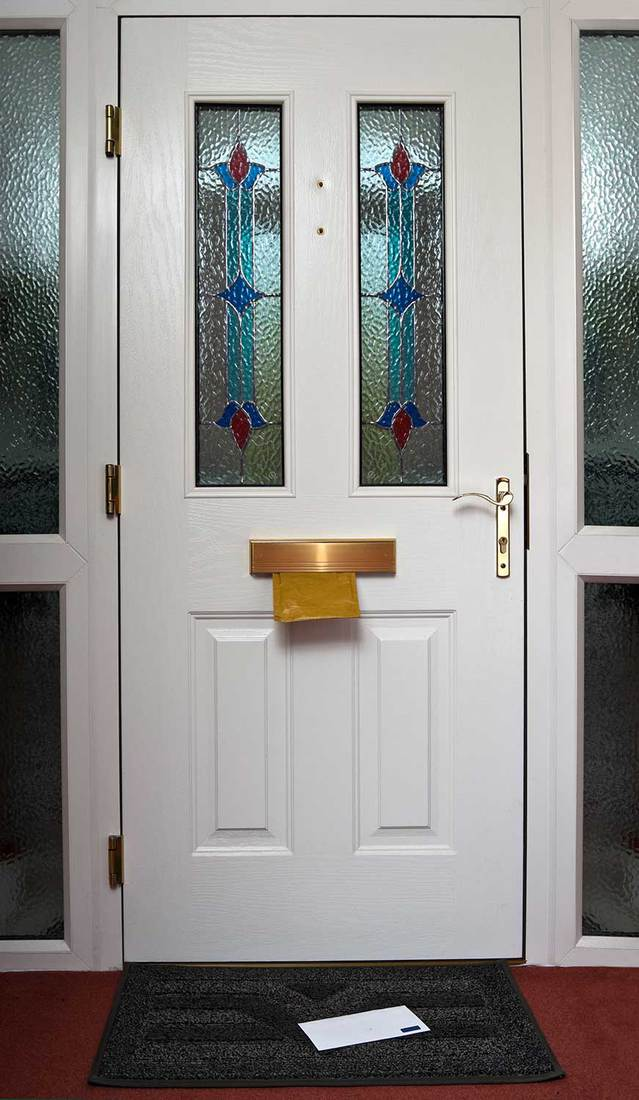 The inside of a stained glass front door with a letter in the in flap and on the doormat