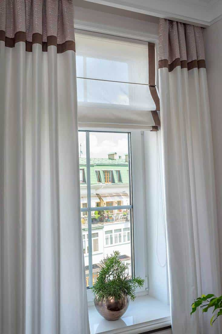 Top floor apartment living room window with white curtain and nice view