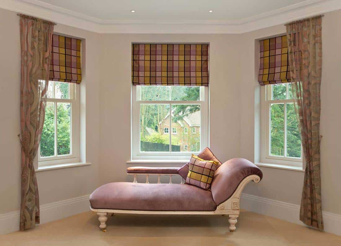 Traditional pink chaise longue in the bay window of a girl's bedroom in a modern new home