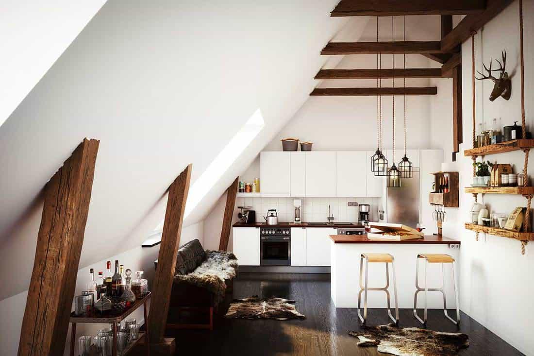 Warm and cozy scandinavian style attic kitchen interior in a loft apartment