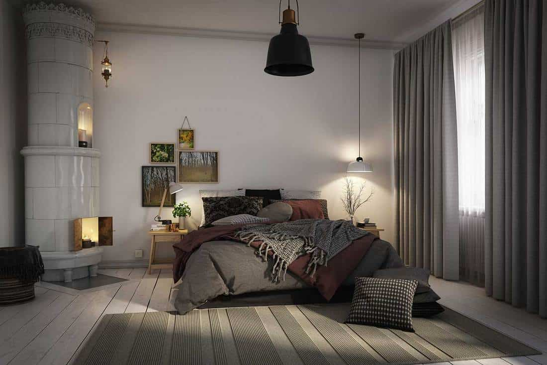 Warm and cozy scandinavian style bedroom interior with grey curtains and fireplace