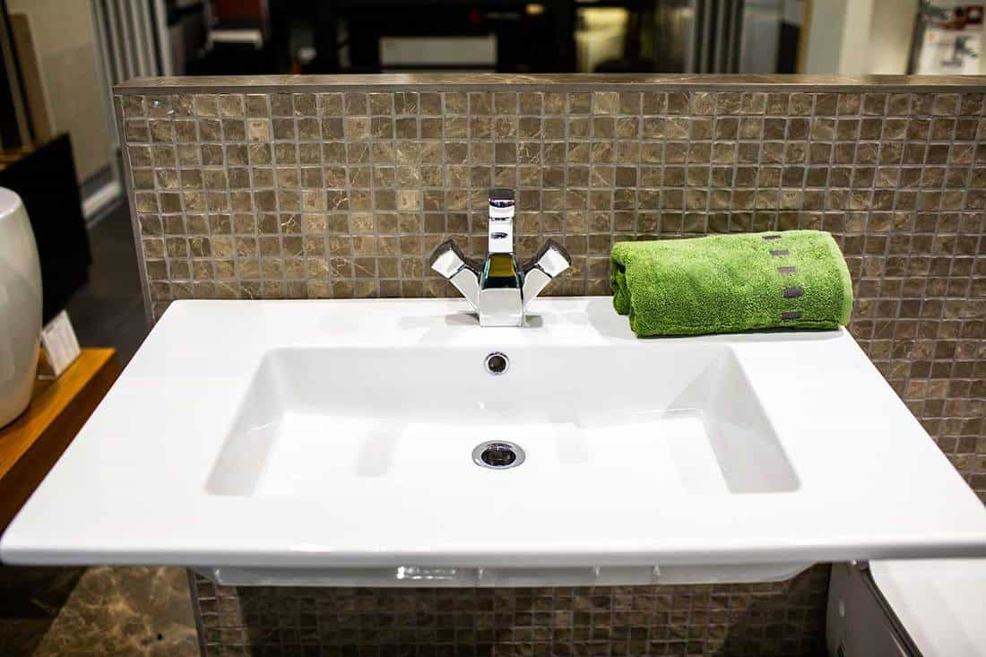 White ceramic bathroom sink with a small rolled green towel on the right side of the faucet