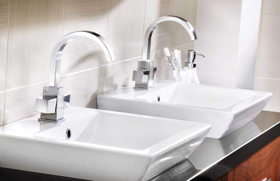 White ceramic bathroom sinks with white tiles and toiletries