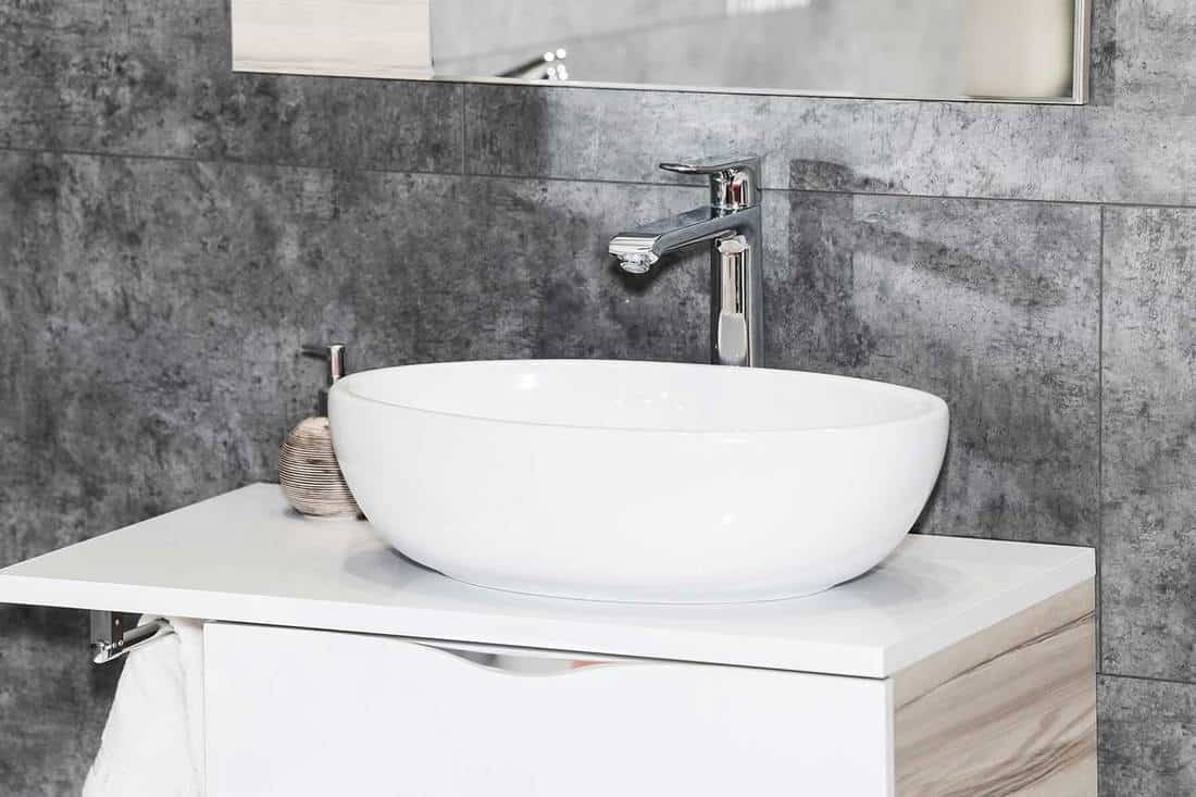 White ceramic sink with chrome faucet and grey marble wall in modern style bathroom