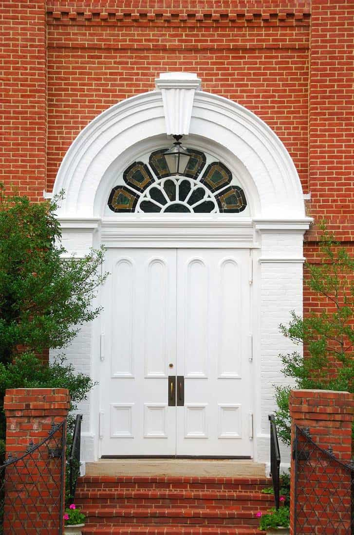 White church doors with a stained glass archway and a red brick walkway with foliage