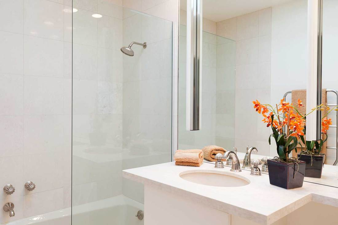 White modern bathroom interior with shower, orange towel and plant on sink