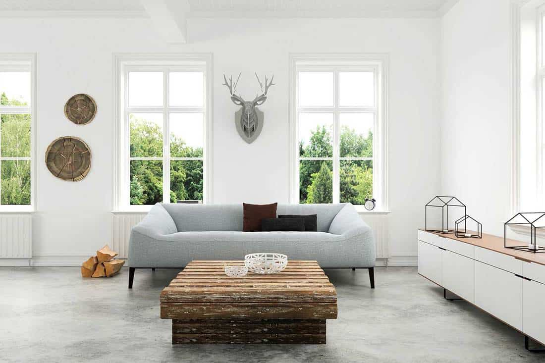 White modern living room interior with comfortable gray sofa, windows showing green nature scenery, concrete polished floor and rustic wooden coffee table