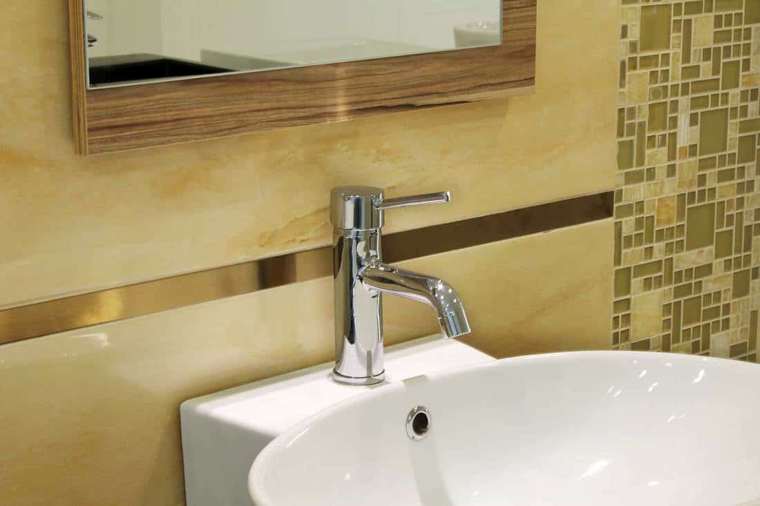 White sink with chrome faucet on yellow wall design