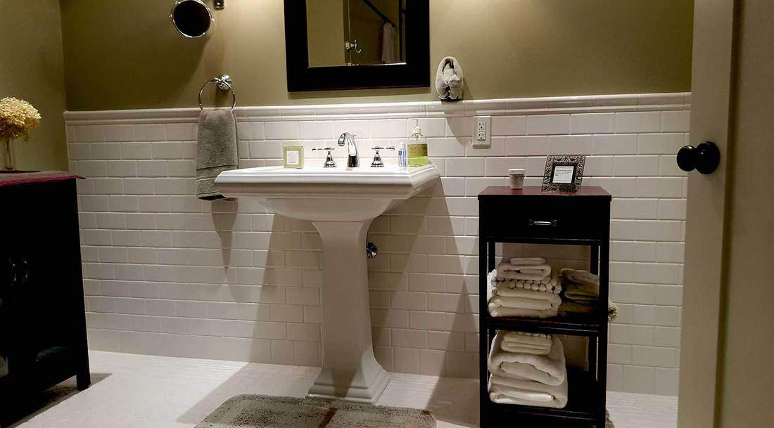 Domestic bathroom interior with white tiles, cherry wood cabinets, mirror and standing sink