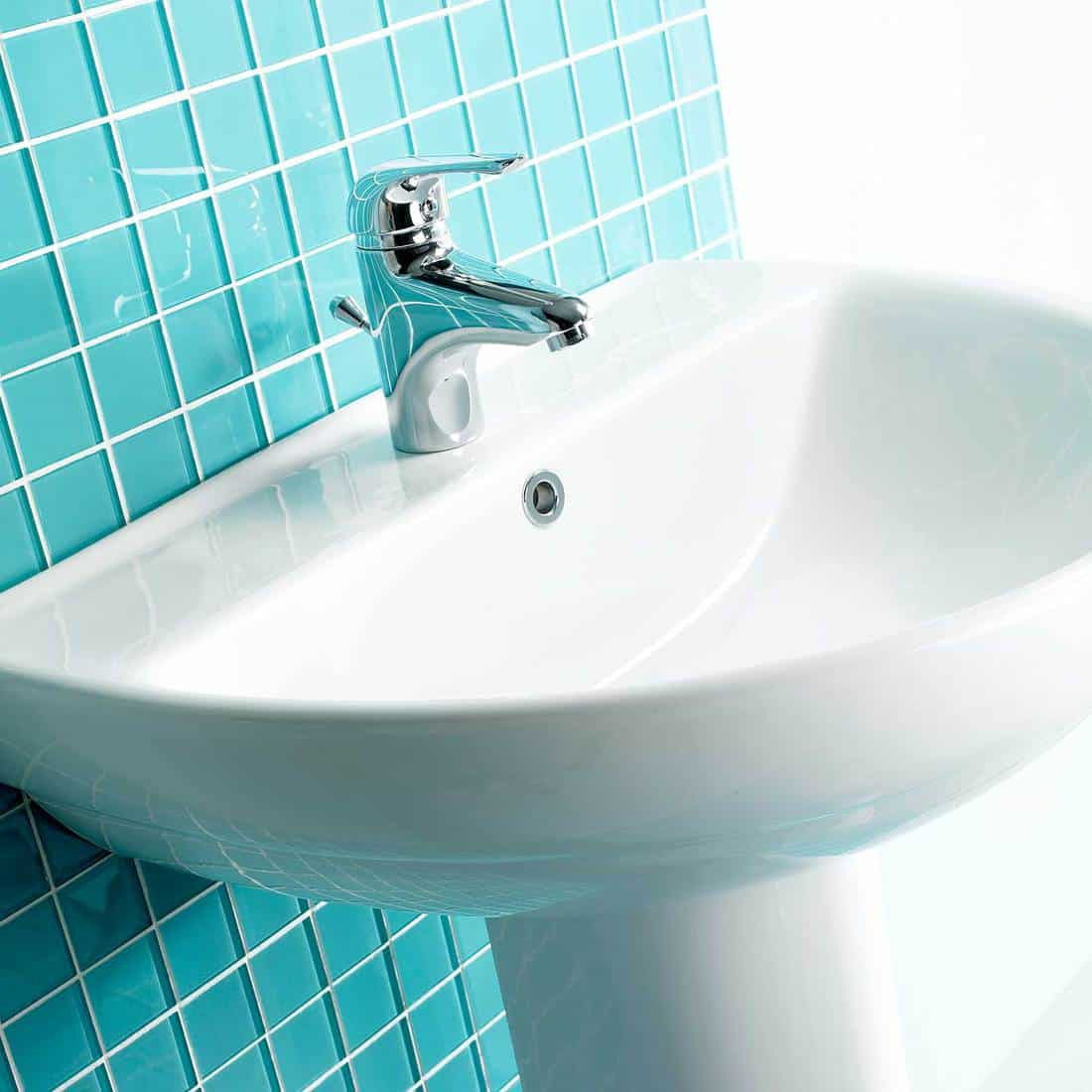 White wash basin with chrome faucet and teal wall tiles