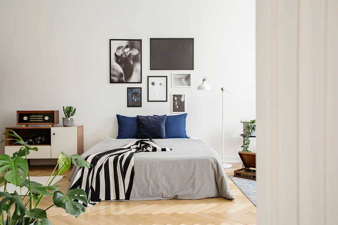 White wooden commode next to bed with dark blue pillows, grey duvet and striped black and white blanket in bedroom with framed art gallery on the wall