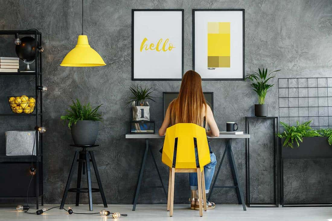Woman working in a black and yellow themed home office