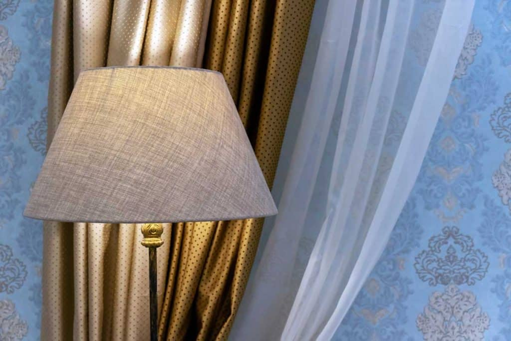 Beige floor lamp on a background of golden curtains and white tulle