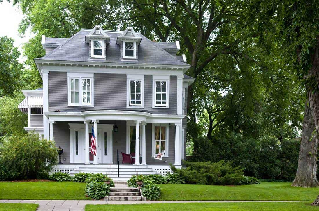 A traditional home with front porch, lawn and stairway