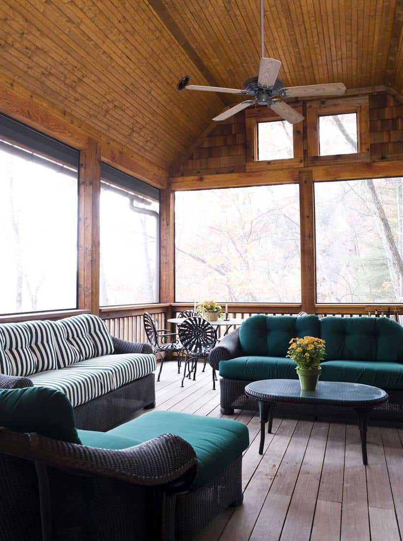 A wooden screened in porch with patio furniture