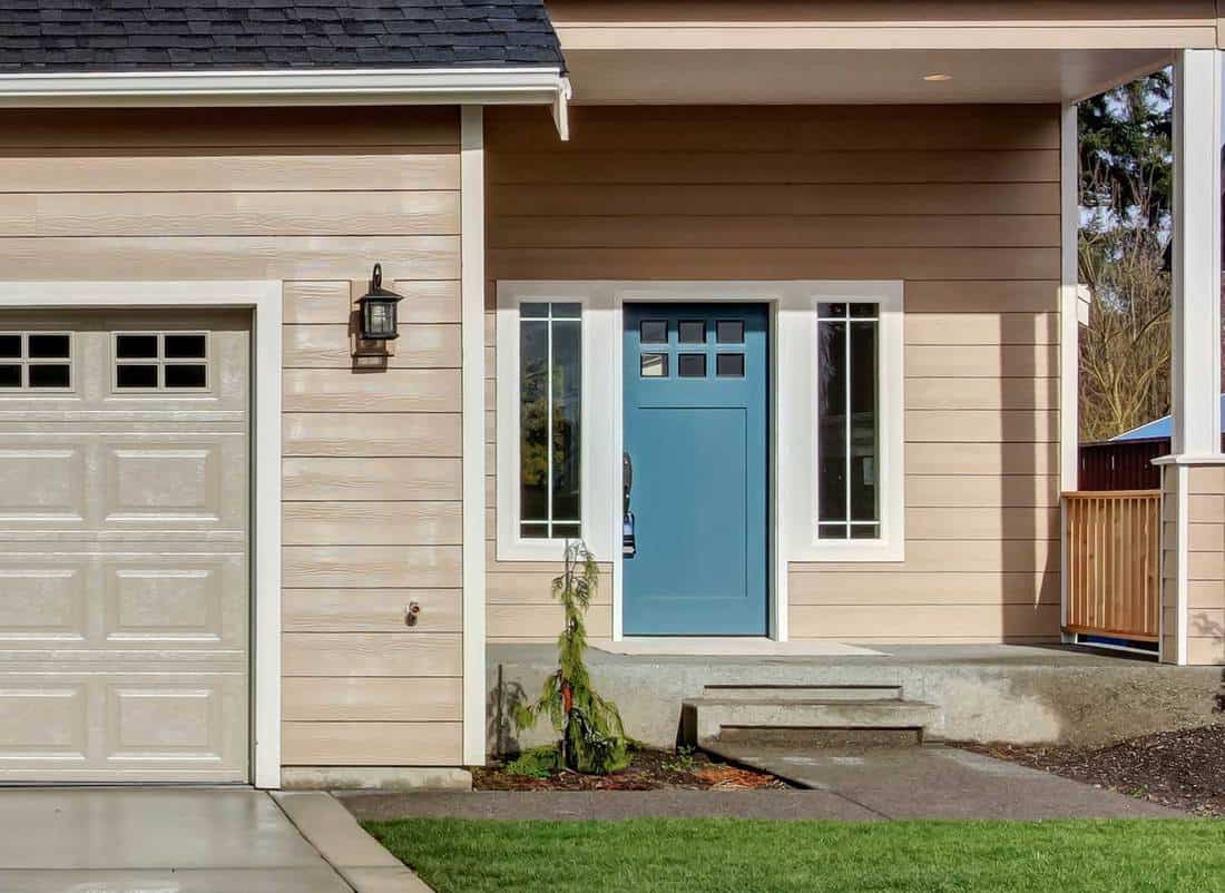 American beige house with teal front door beside garage and driveway