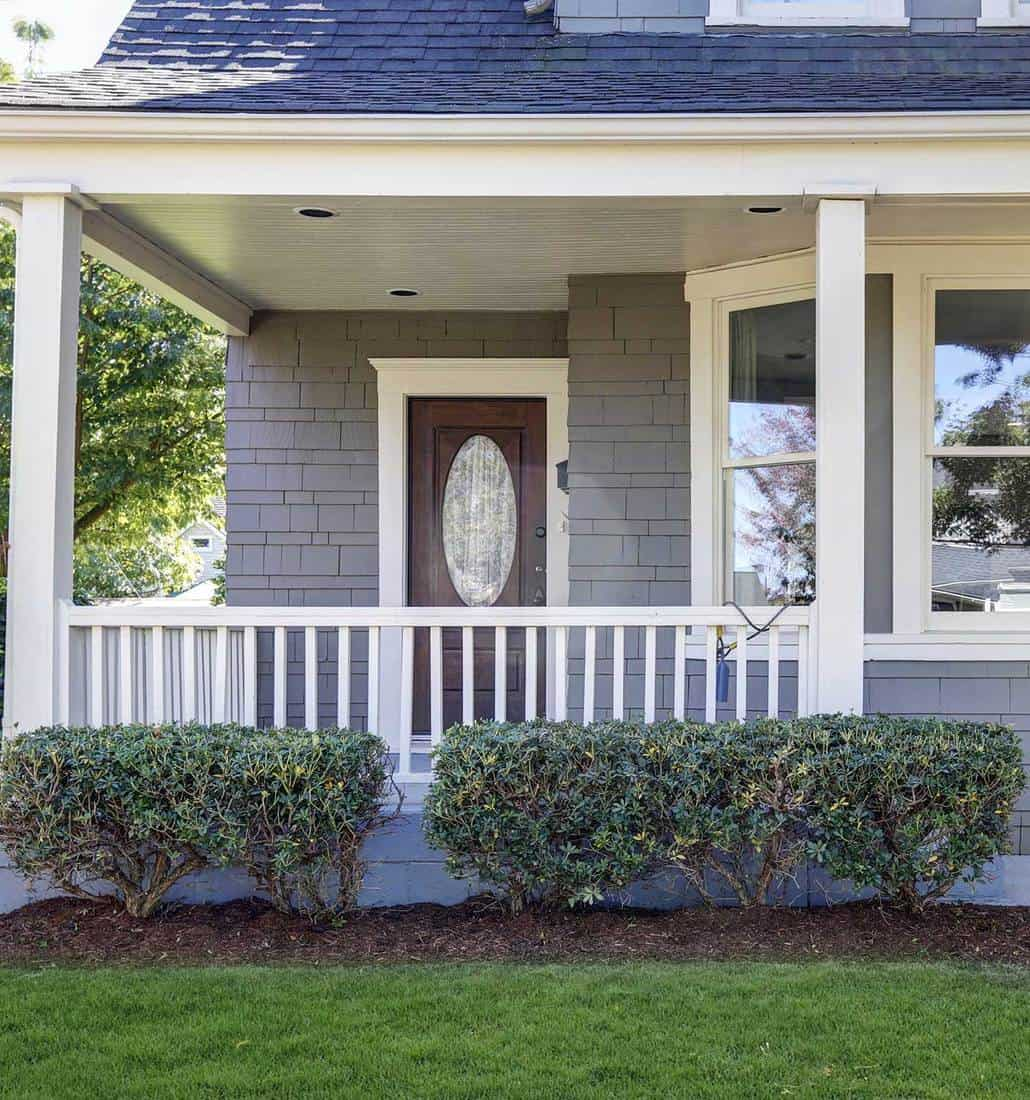 American blue house with well kept front yard and hardwood door with glass in the middle