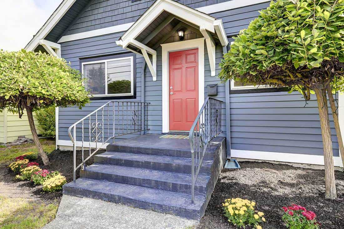 American house exterior in grey color with red front door and blue stairs on walkway