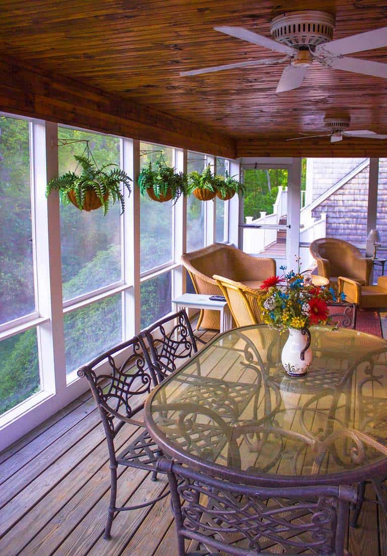 An indoor screened in porch with plants hanging from the side and a tinted yellow glass table with chairs