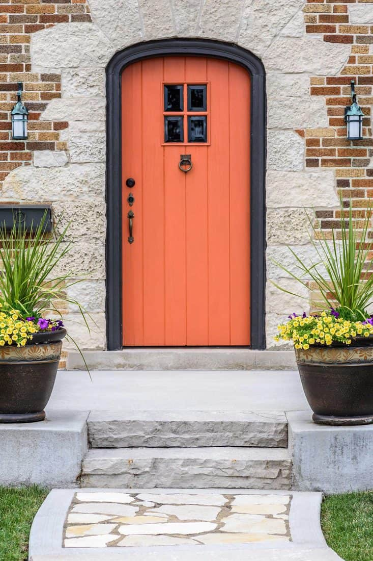 Arched orange door with small windows and brick themed walls