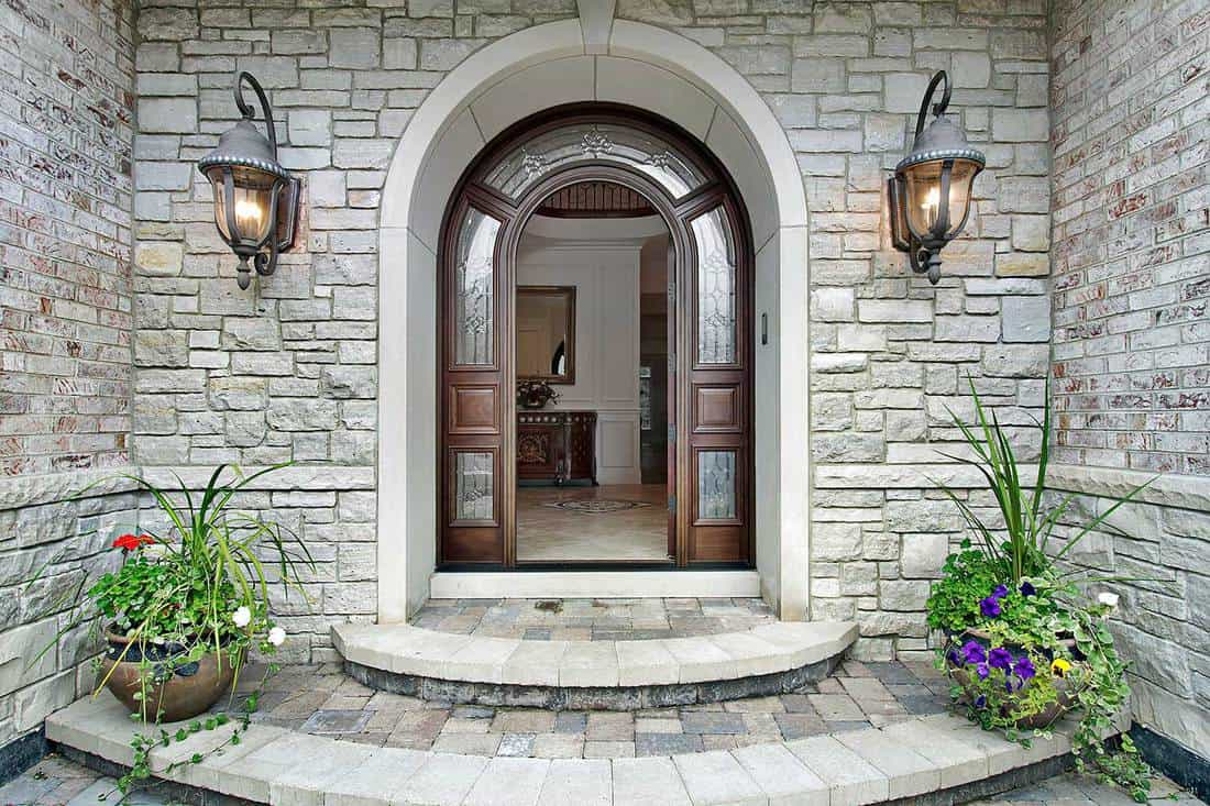 Arched stone entry of luxury suburban home with timber door