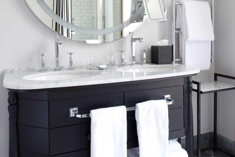 Bathroom vanity against a white wall with towels, tissue and big round mirror