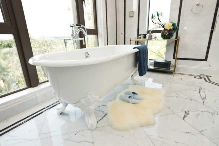 Bathtub near window and slippers on bath rug