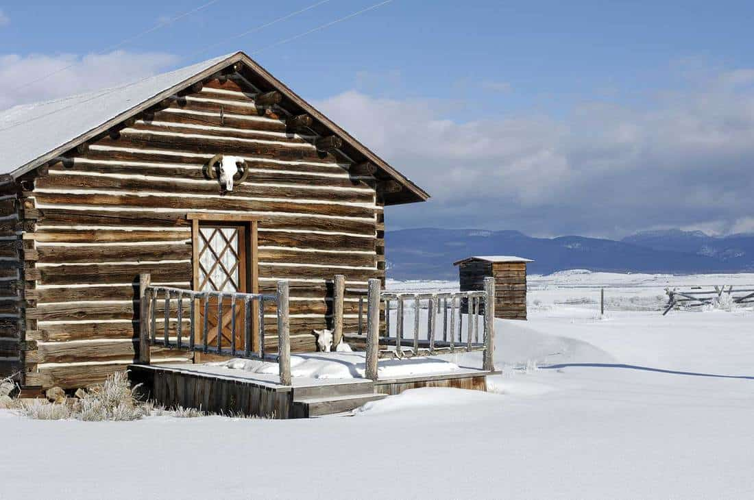 Beautiful front porch of a snow covered cabin