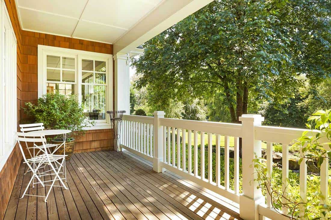 Beautiful front porch with red brick walls, wooden floor, table and chairs on a lovely summer day