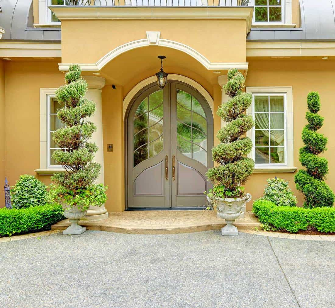 Beautiful glass door house entrance with column porch and spiral topiary opposite each column