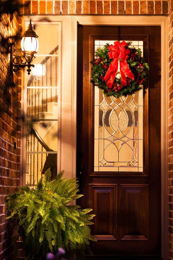 Beautiful holiday wreath on front wooden door of a modern brick home