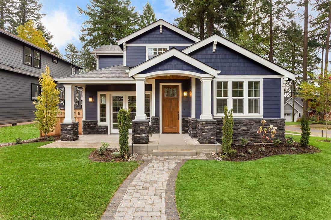 Beautiful luxury home exterior with green grass, landscaped yard and walkway to front porch