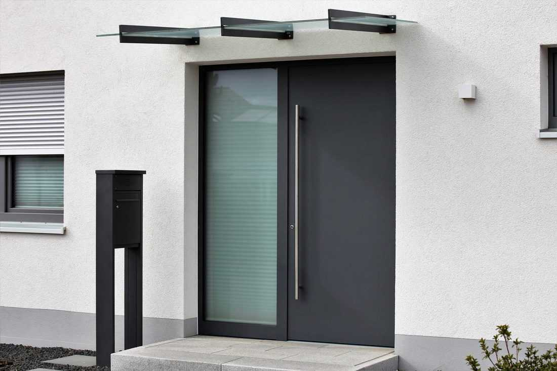 Black aluminum pivot door with long handle with trellis holding glass roofing