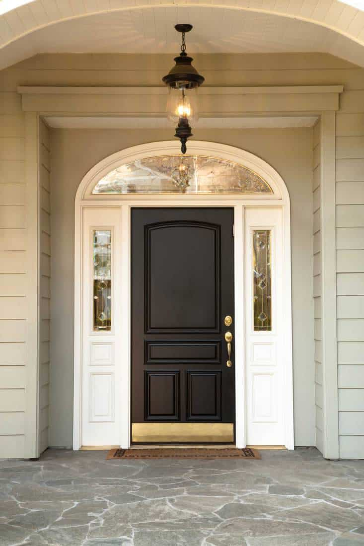 Black door with arched window and white colored framing