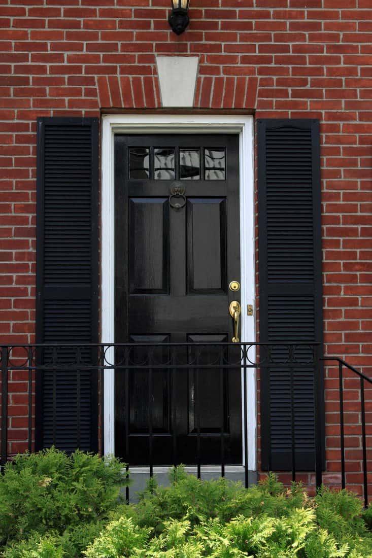 Black door with french door type secondary door and brick walls