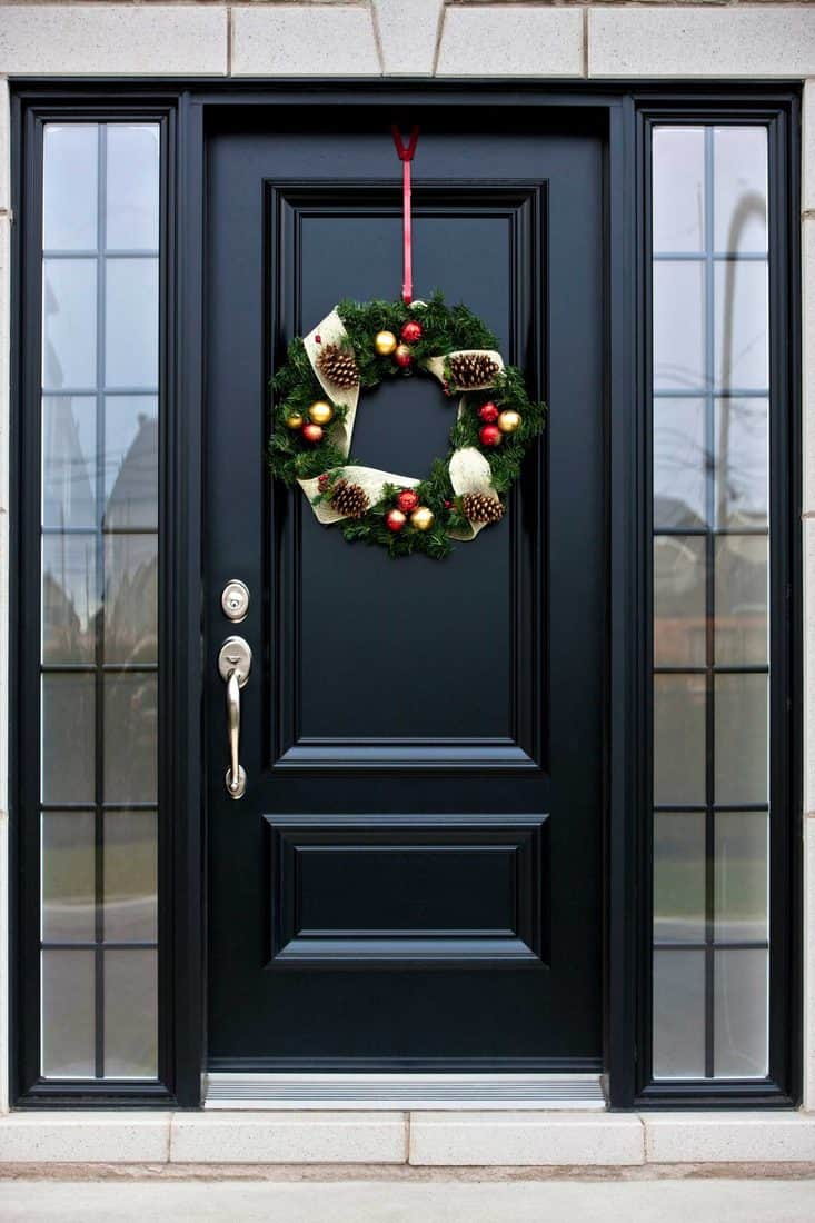 Black door with glass sidings and a hanging Christmas wreath