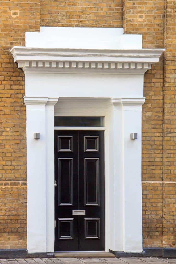 Black door with white entry way and brown brick walls