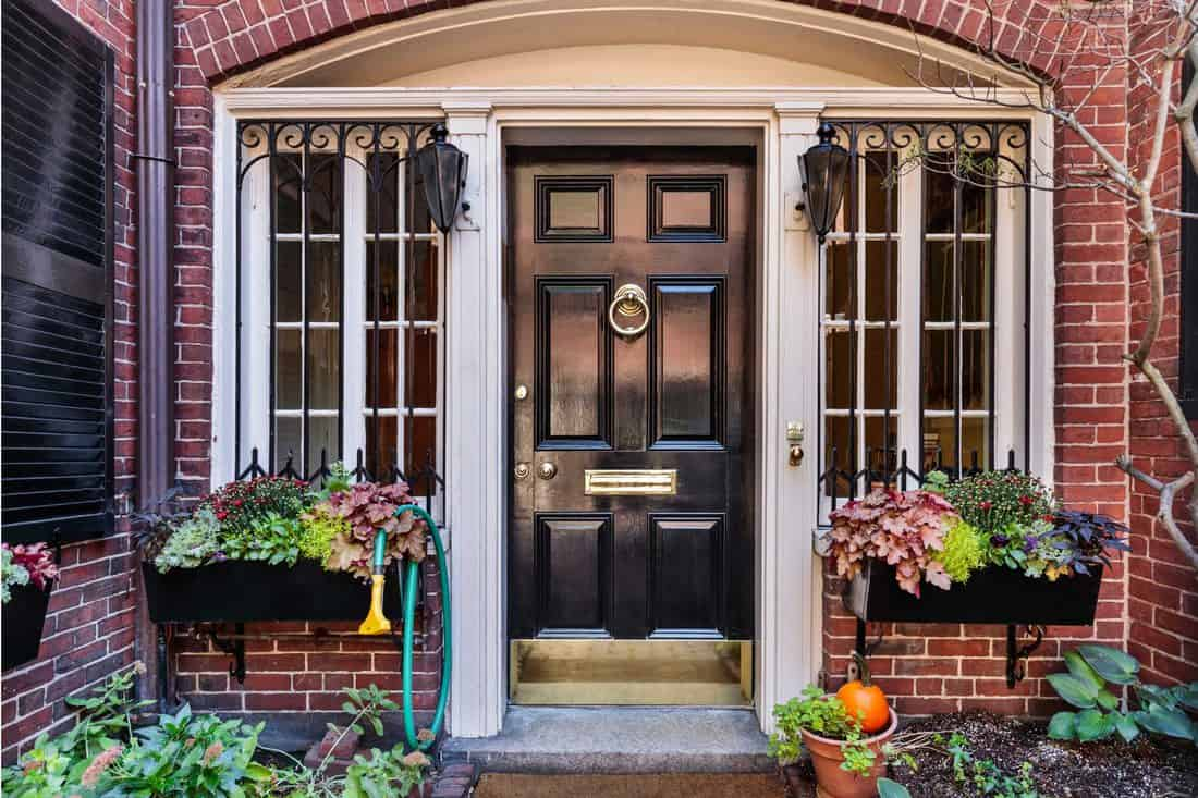 Black door with white sidings and arched header with hanging plant boxes at windows