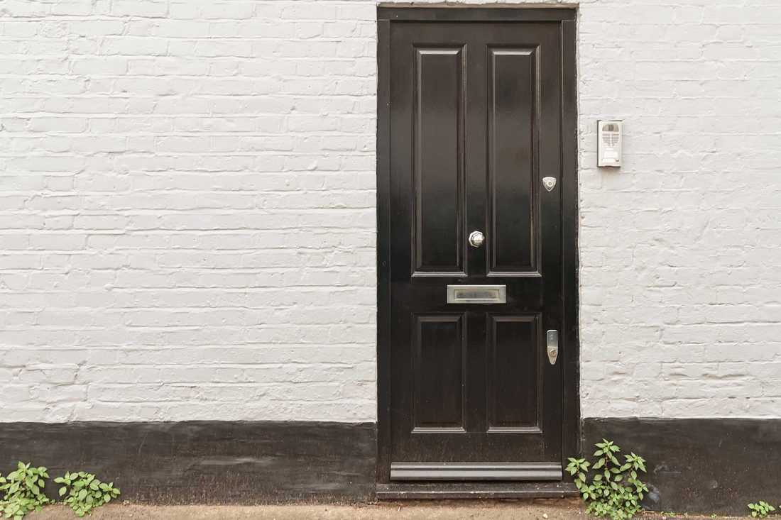 Black door with white wall and brown colored base