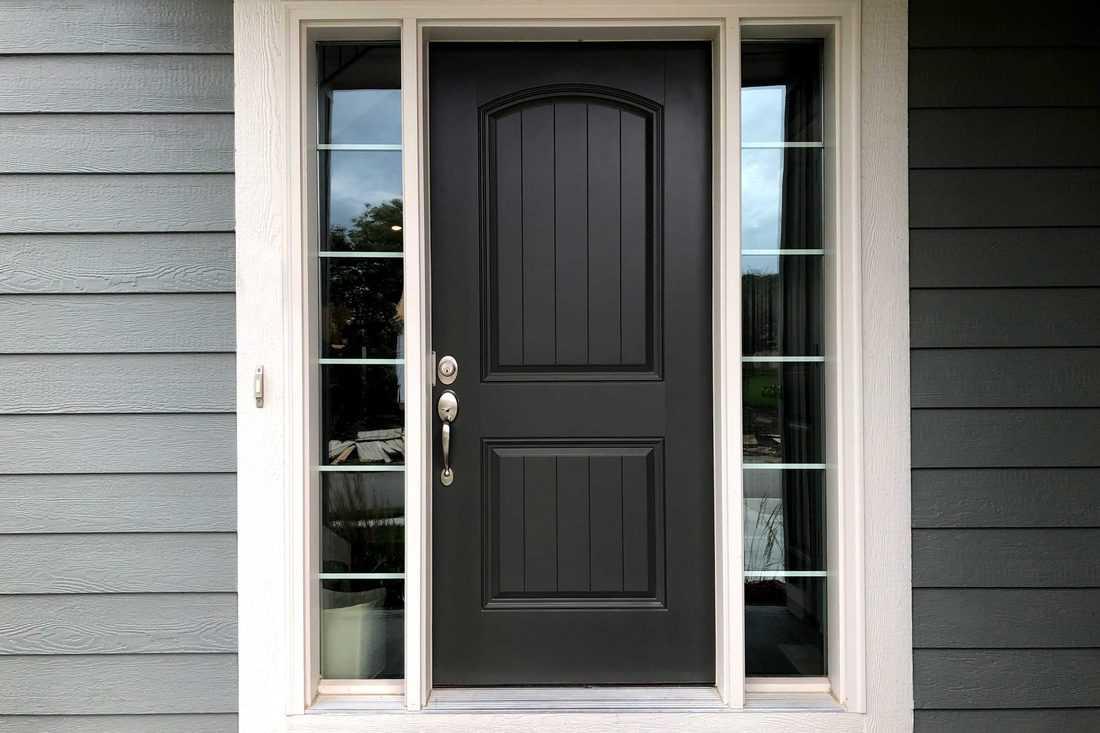Black door with window sidings and grey wooden walls