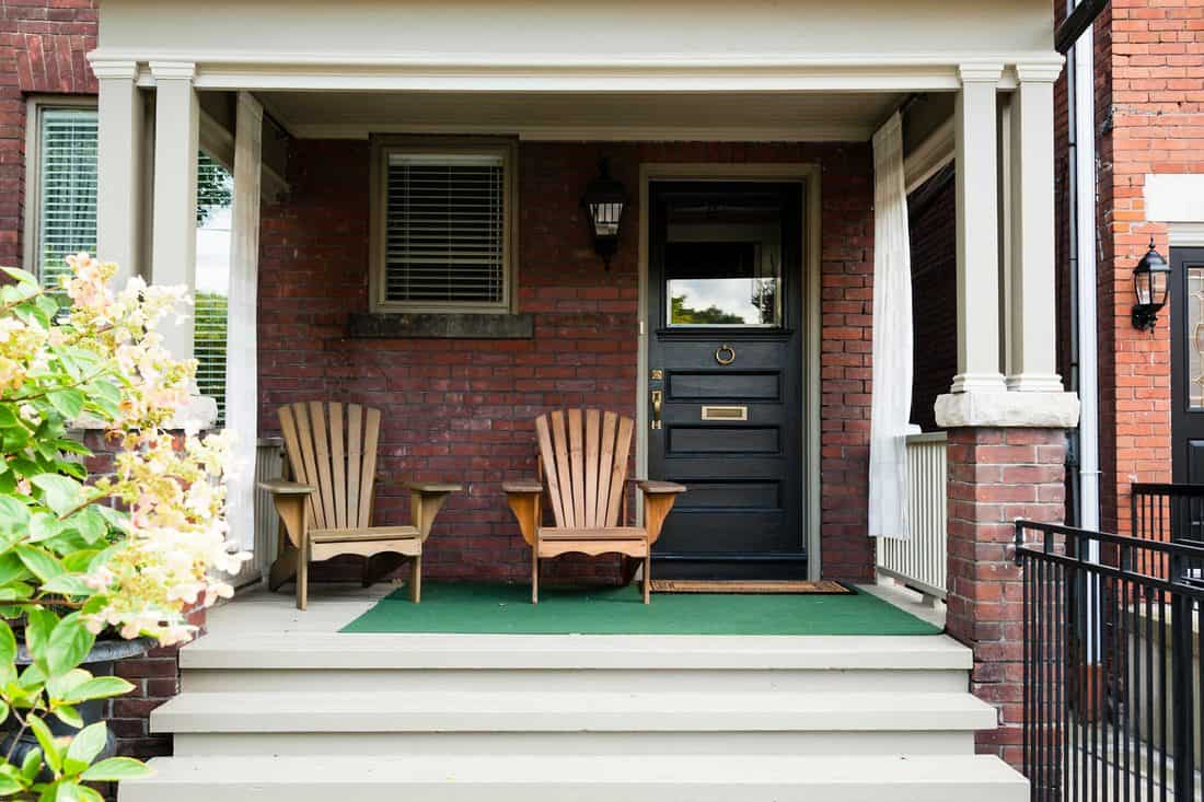 Black door with wooden chair next to it and three step chairs