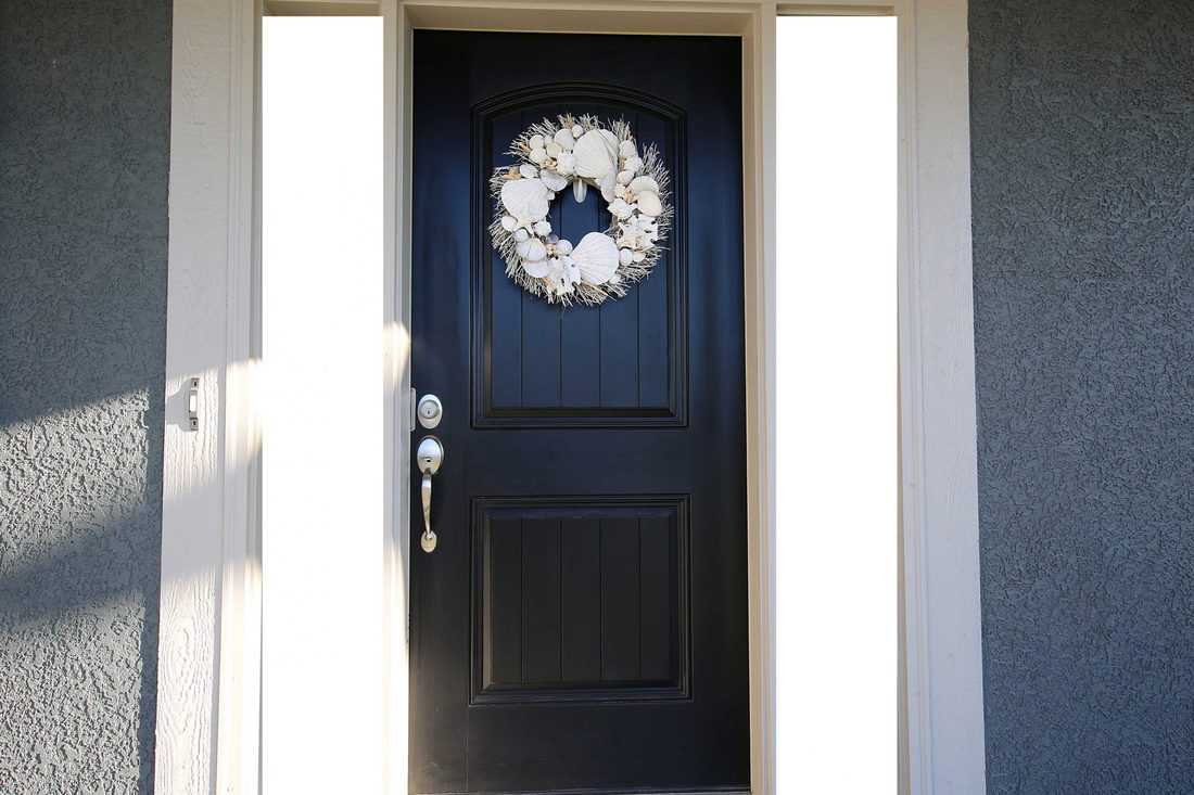 Black door with wreath and bright colored sidings and white wooden door jamb