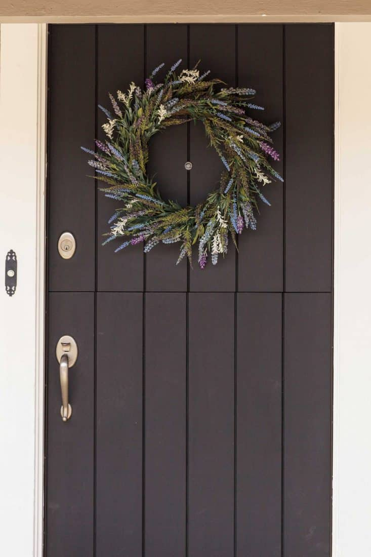 Black door with wreath made with flowers