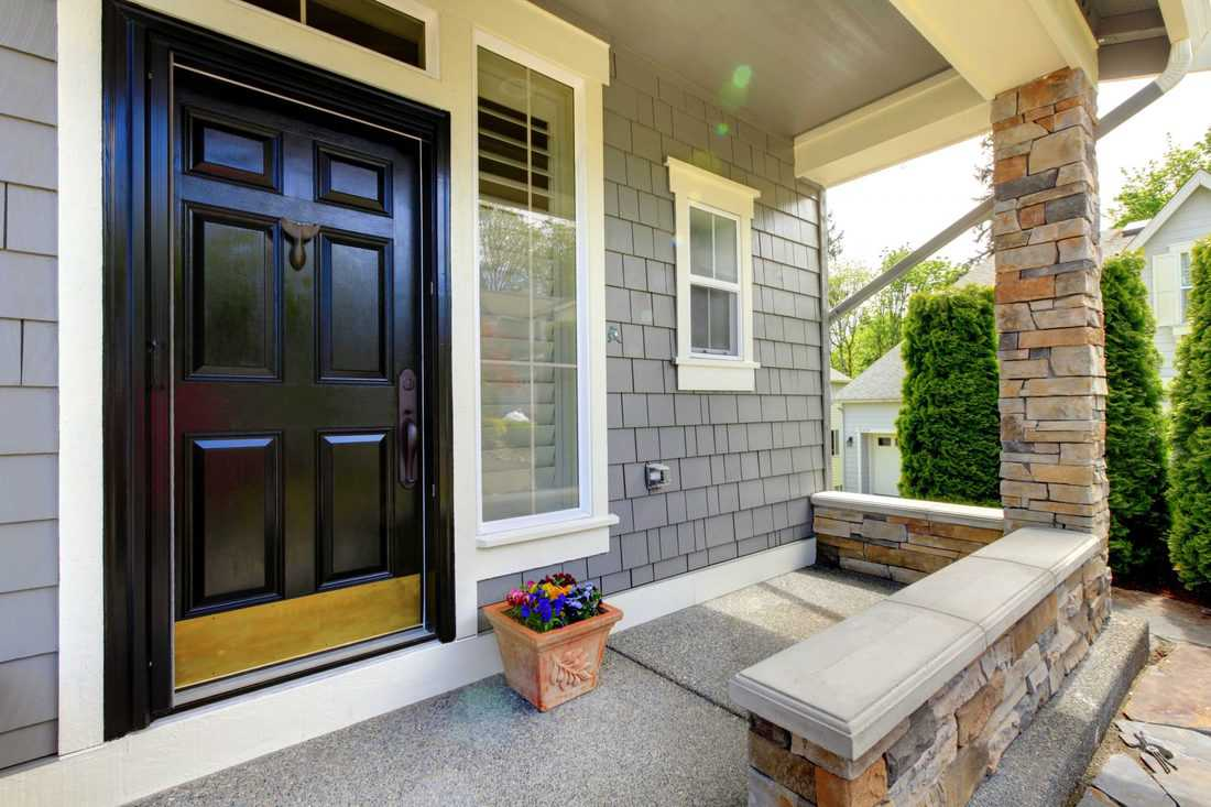 Black double door and balcony made with decorative stones