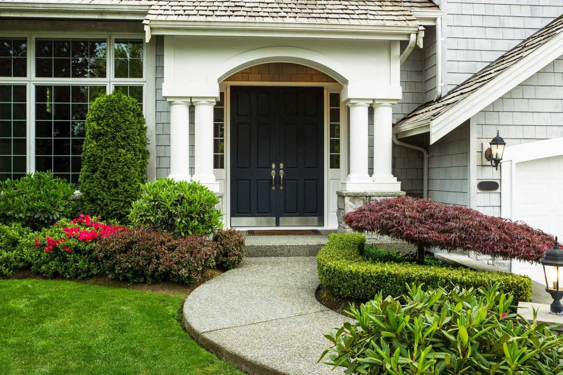Black french door with circular column shelter and wash-out pebble path walk