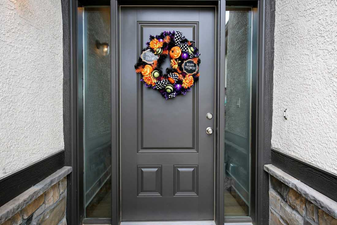 Black modern door with glass sidings and wreath made with cool materials
