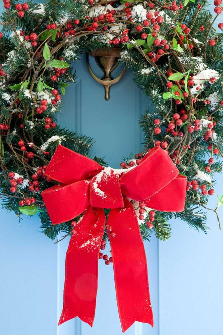 Blue door with christmas wreath attached with red ribbon and red berries for front door decoration