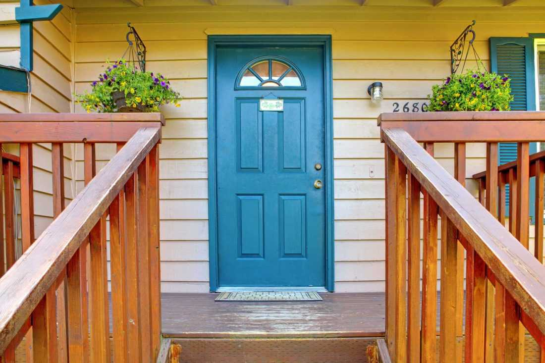 Blue door with wooden railings and hanging plants