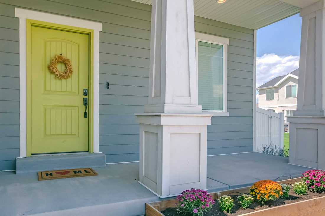 Blue green colored porch with yellow green door and triangular shaped columns